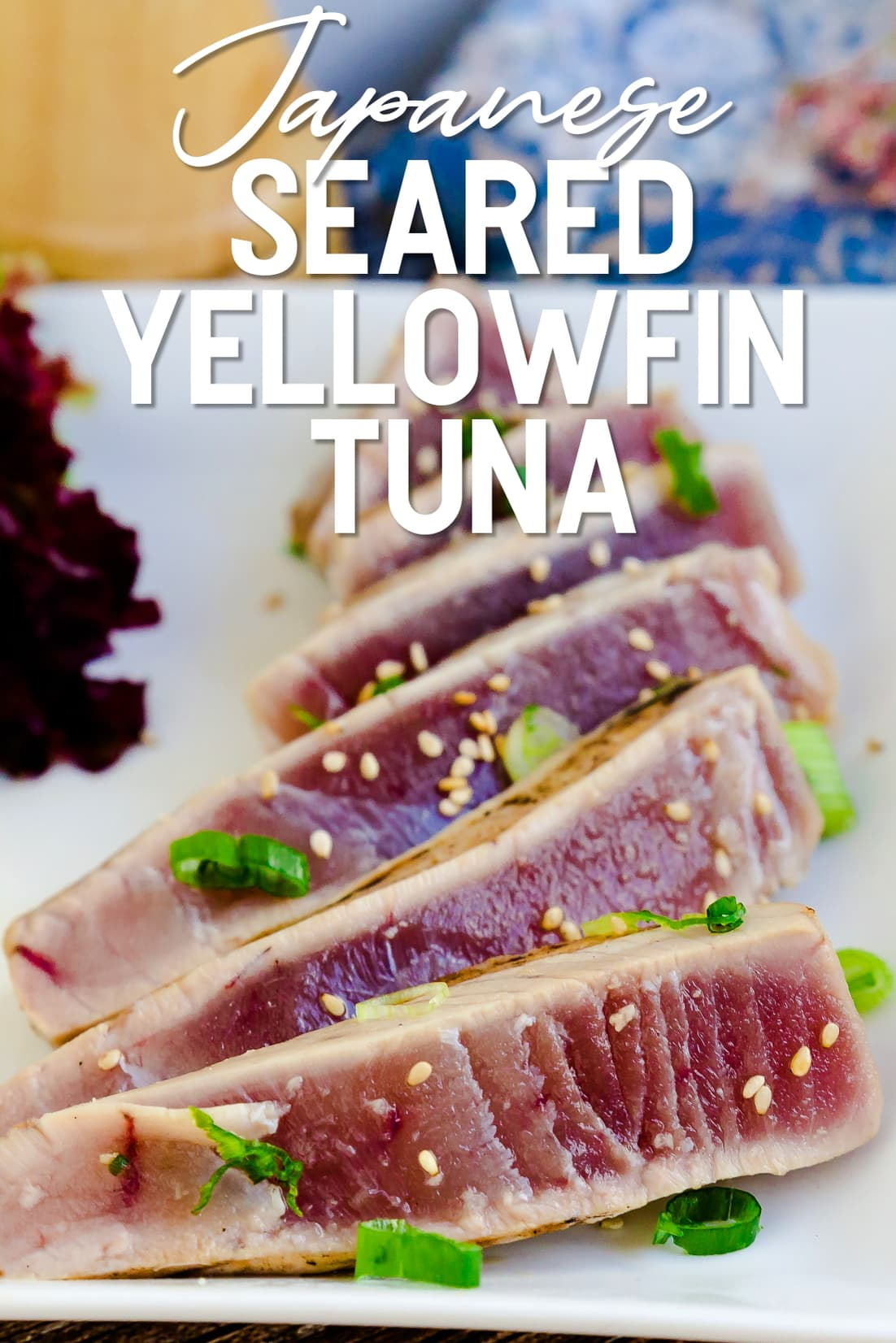 Seared Yellowfin Tuna served on a plate with sesame seeds and green onions sprinkled on top