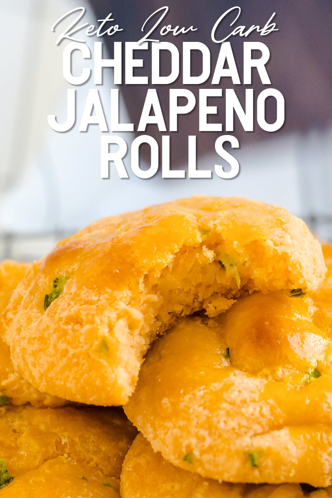 Keto Cheddar Jalapeno Rolls stackeed on top of each other with a bite taken