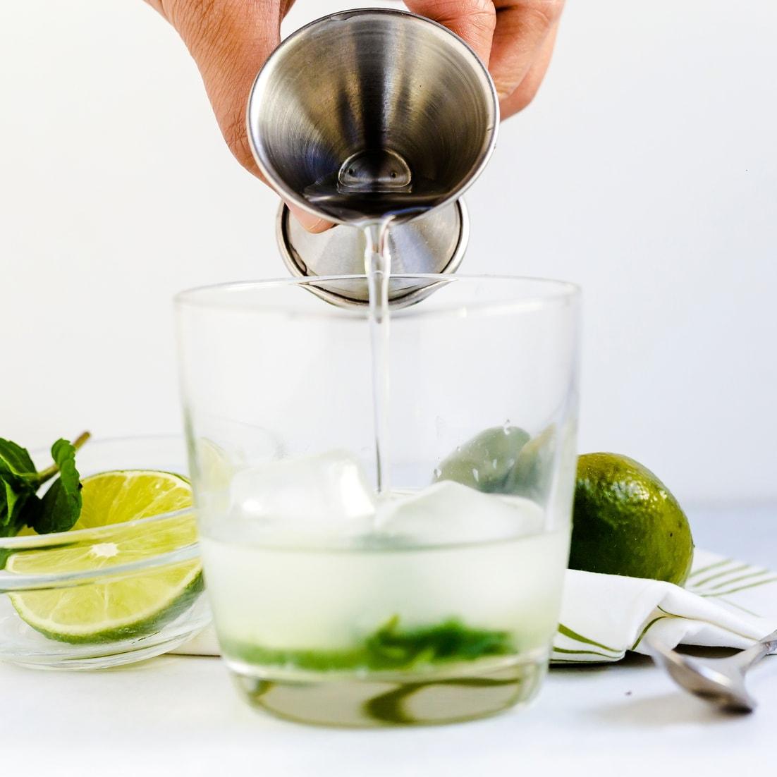 White rum being poured to make keto mojito
