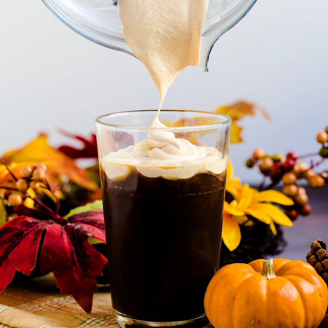 Keto Pumpkin Cream being poured into a glass tumbler