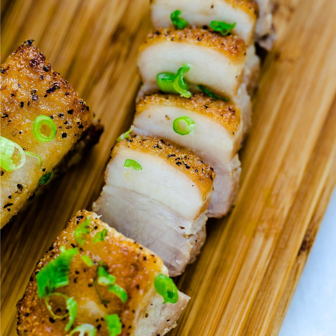 Crispy Pork Belly on serving plate with green onions sprinkled on top