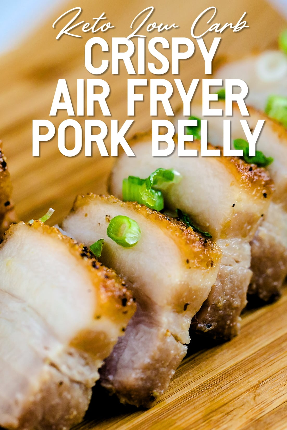 Crispy Pork Belly lined up on wooden plank with green onions sprinkled