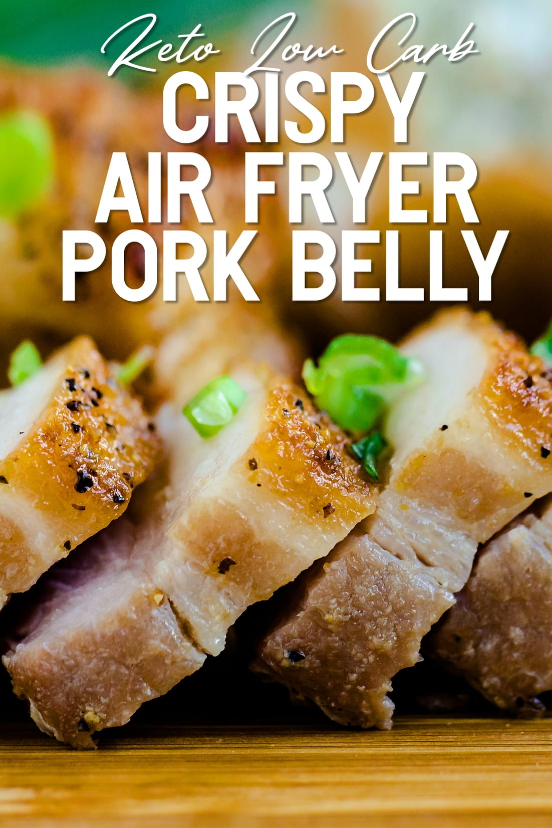 Crispy Pork Belly lined up on wooden plank with green onions sprinkled side shot