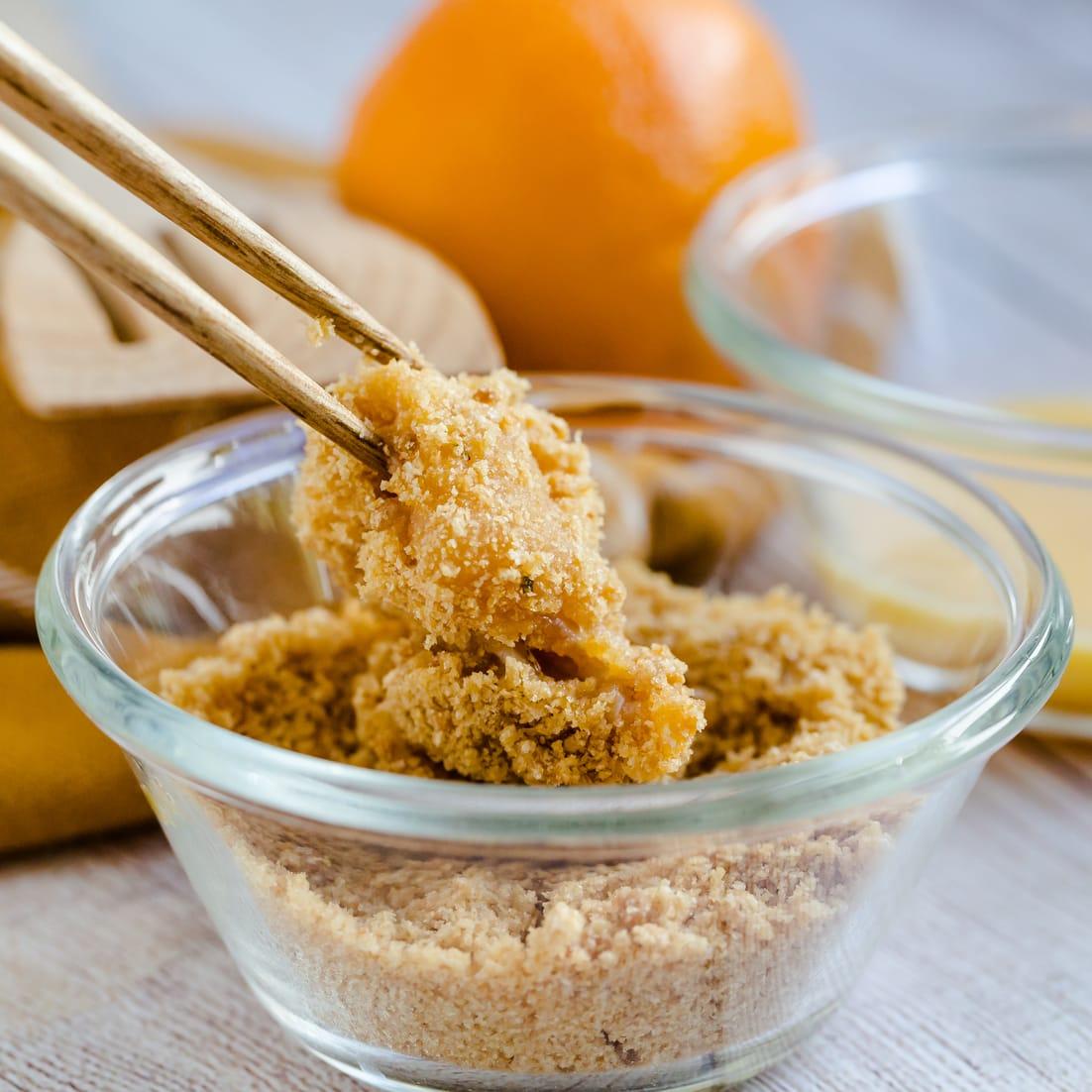 Keto Orange Chicken being dipped in panko pork rinds