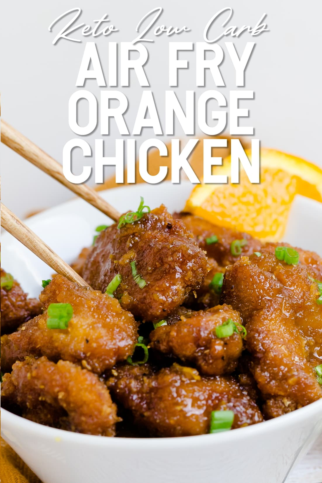 Pair of chopsticks holding a piece of Air Fry Keto Orange Chicken in a bowl