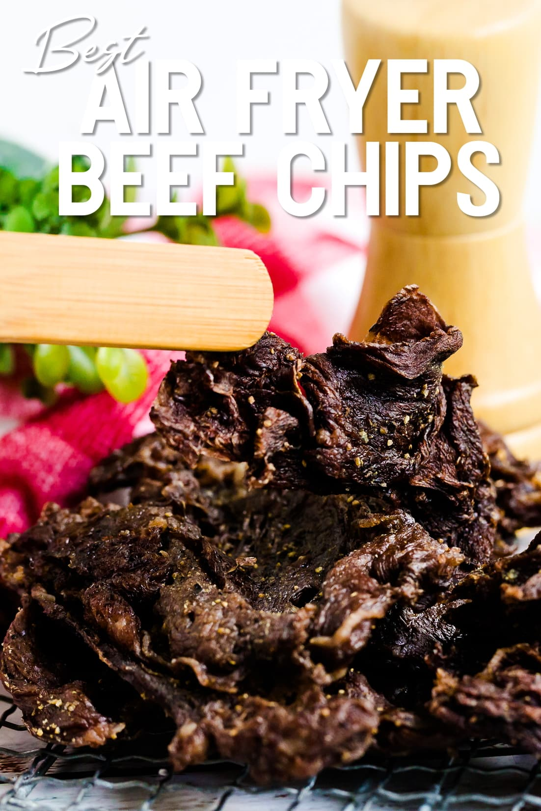 Air Fried Beef Chips being picked up with wooden tongs
