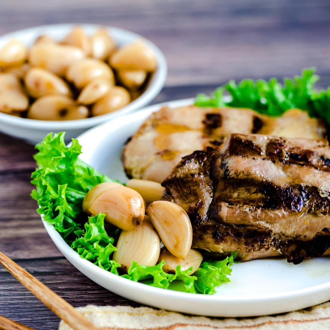 Japanese Soy Sauce Pickled Garlic served with perfect BBQ chicken on green leaf lettuce