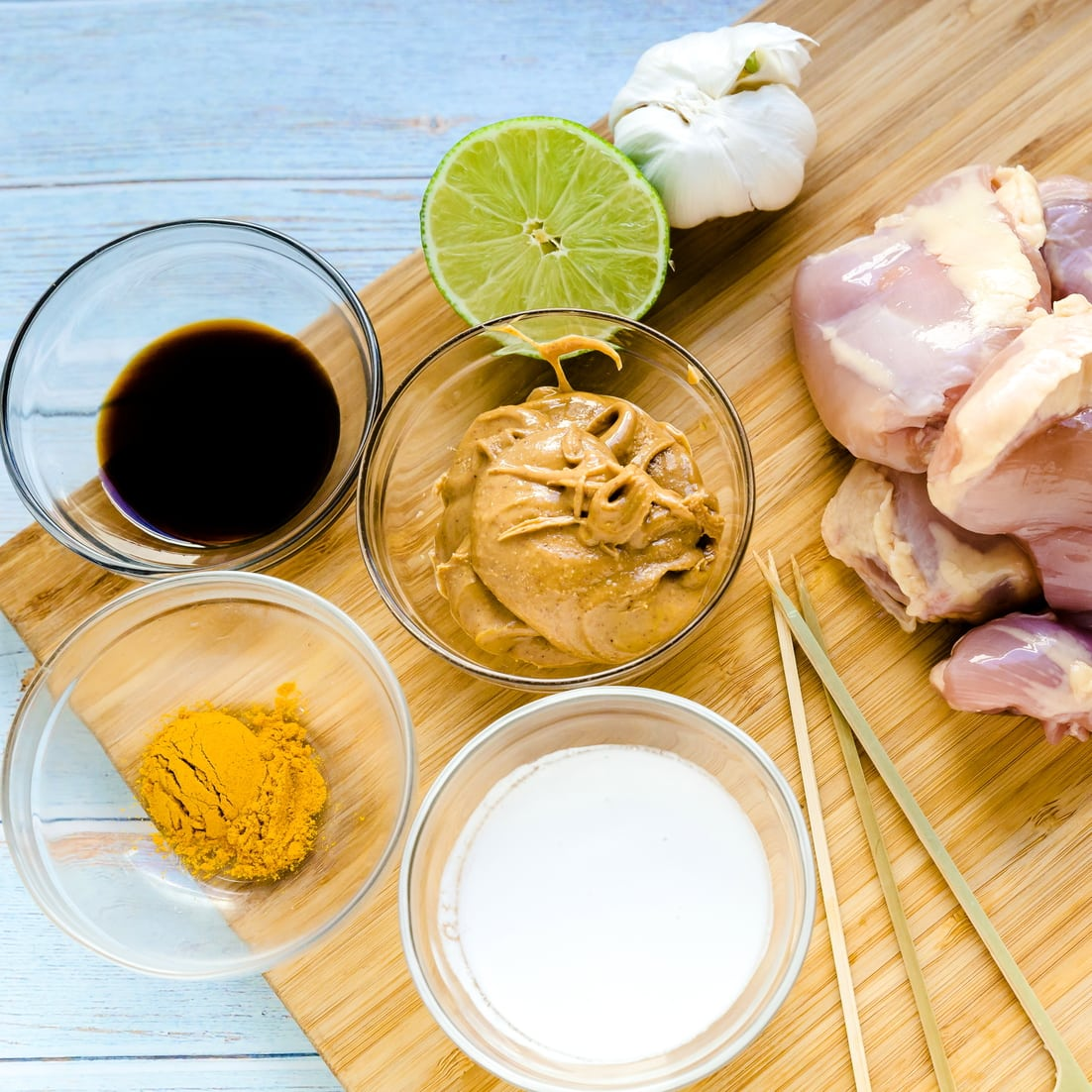 Ingredients for Keto Chicken Satay with Peanut Sauce laid out on wooden cutting board