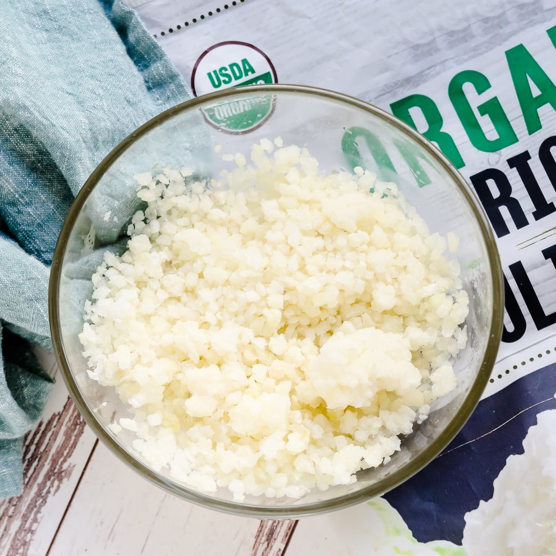 Keto Cauliflower Rice being prepped in a glass bowl