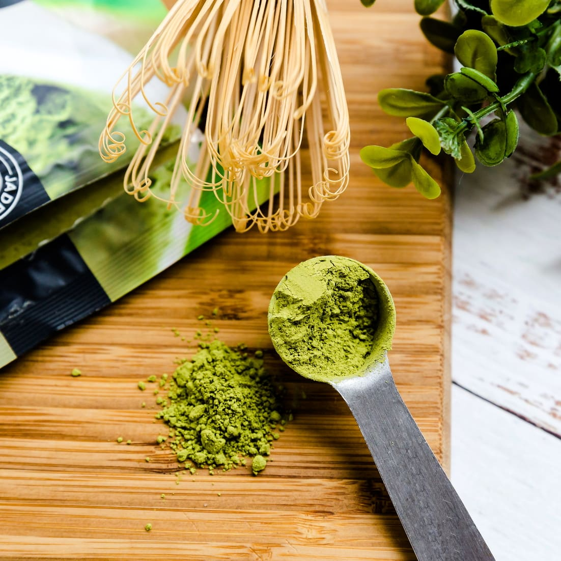 Matcha powder next to wooden matcha whisk