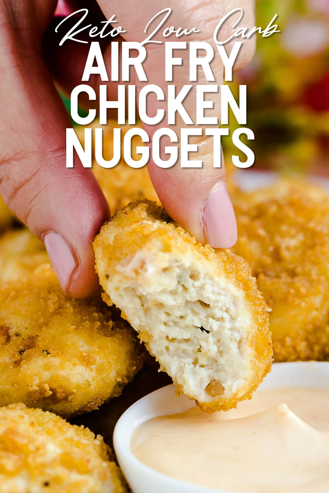 Keto chicken nuggets being dipped into spicy mayo dipping sauce