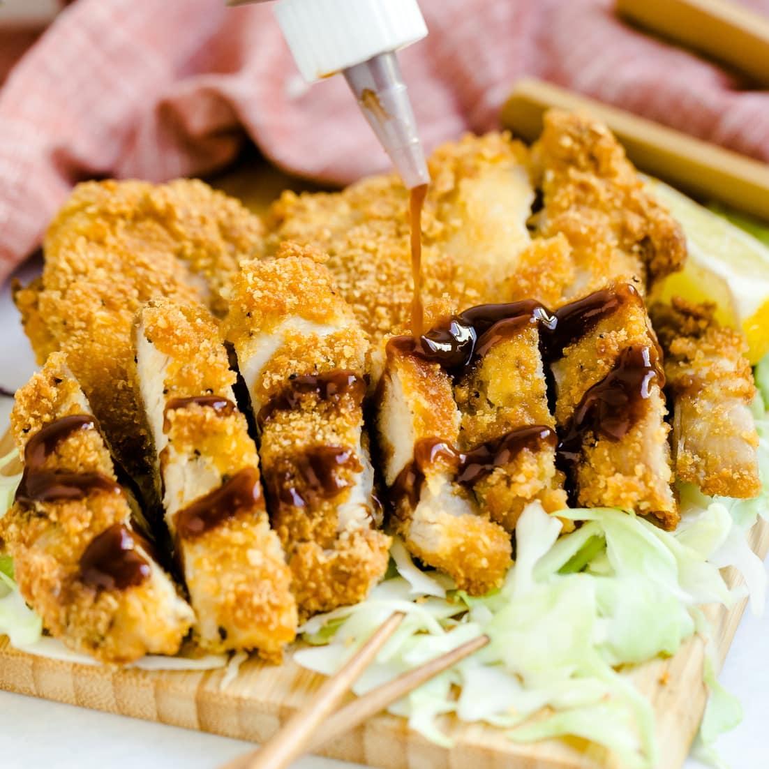Low carb tonkatsu sauce being squeezed over keto tonkatsu