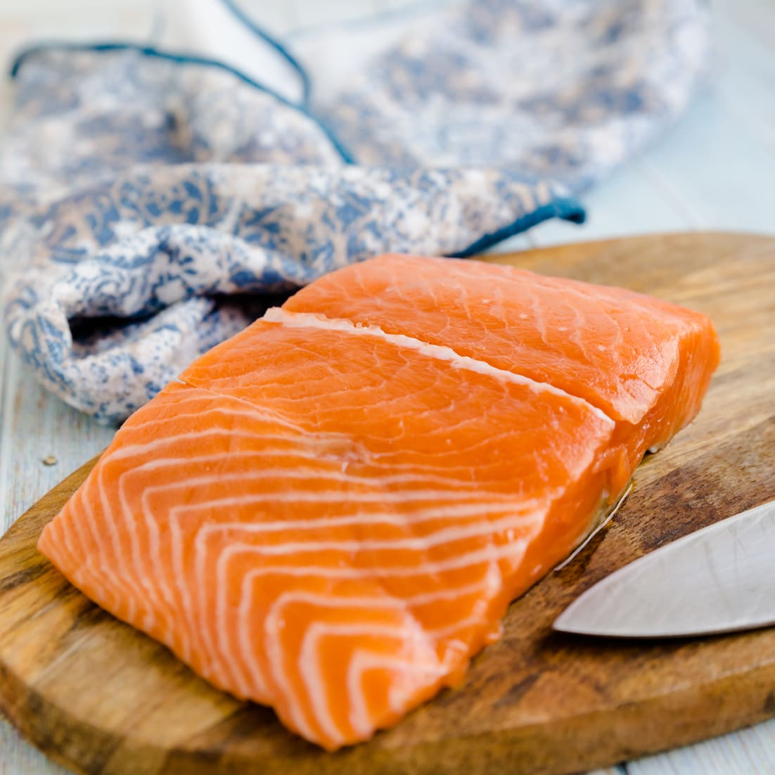 Skinless salmon fillet on a wooden cutting board