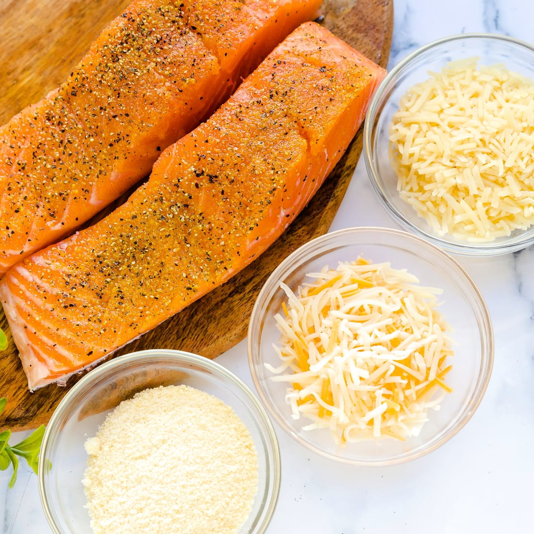Seasoned salmon fillet next to different types of cheeses for baking