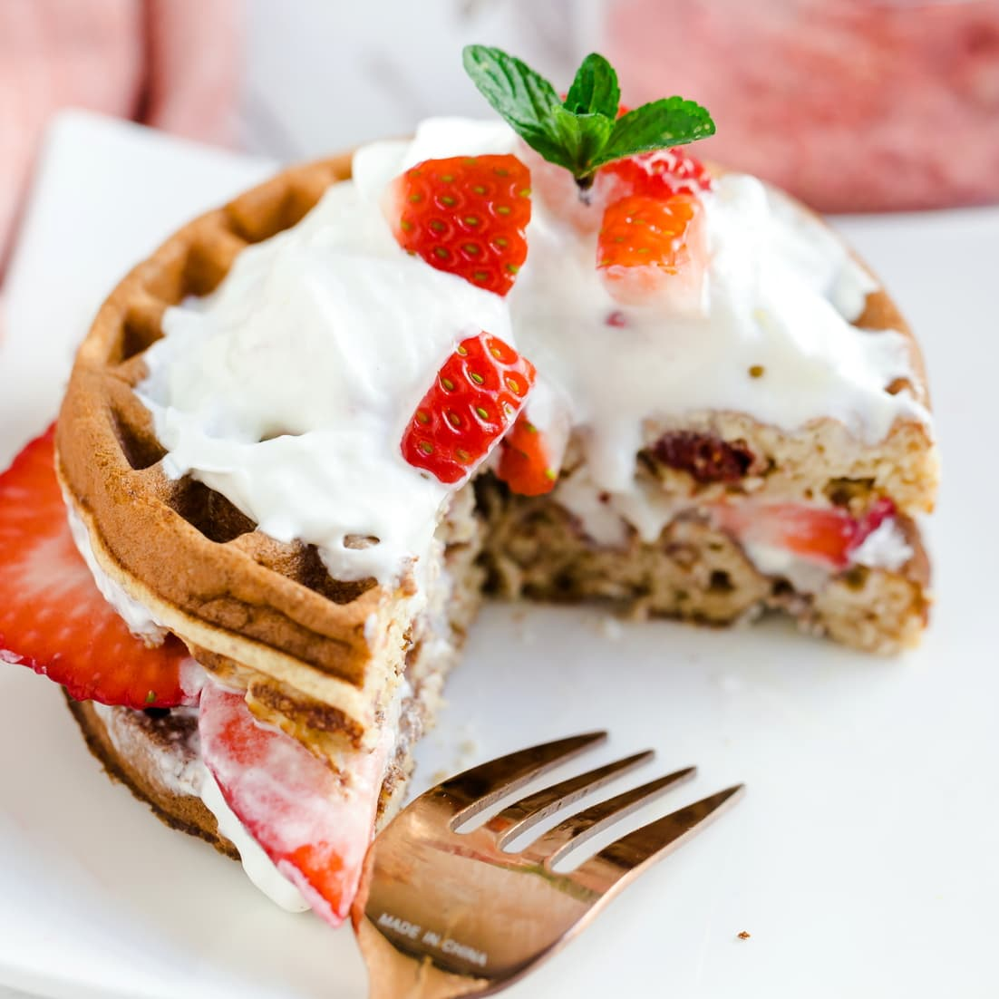 Keto Coconut Strawberry Shortcake Chaffle served with whip cream and sliced strawberries showing cross sectional cut