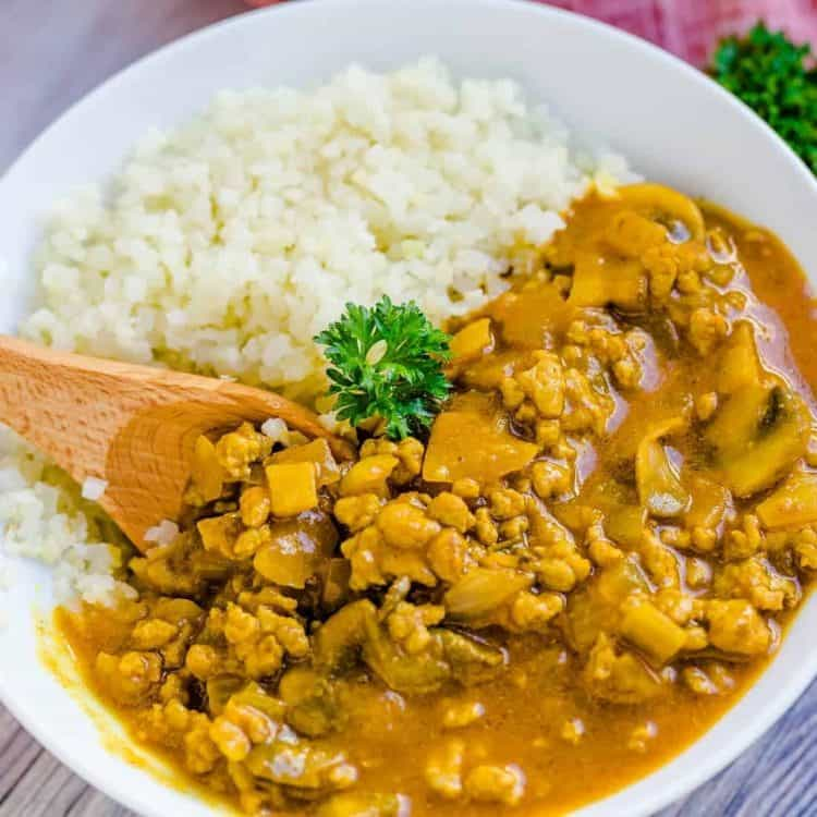 Keto Keema Cauliflower Curry served in a white bowl with wooden spoon