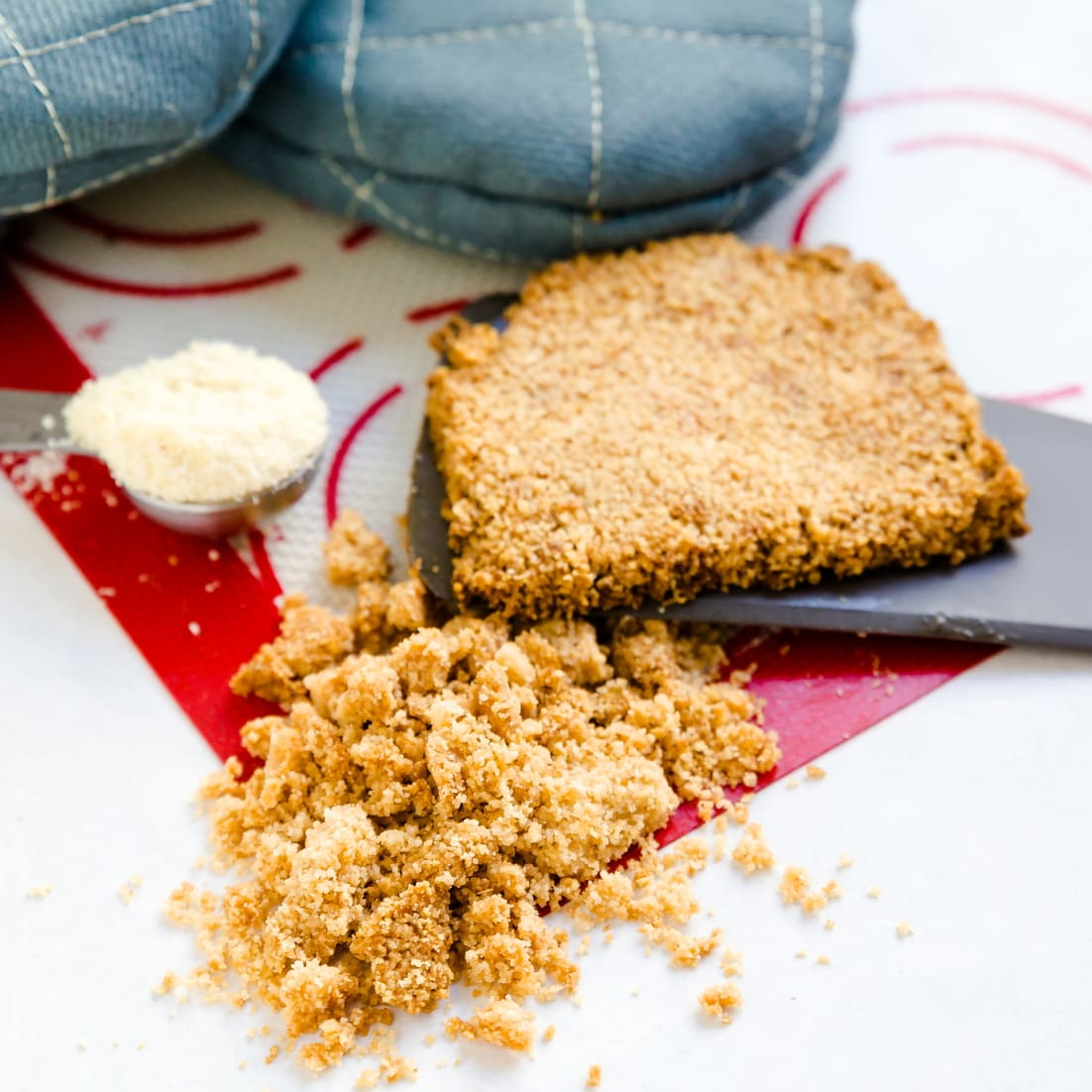 Keto cheese crumble crust on a silicon baking mat
