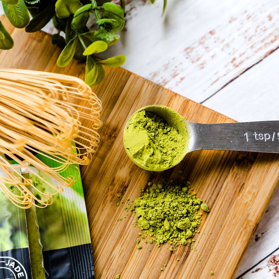 Matcha powder inside a measuring spoon next to a wooden matcha whisk