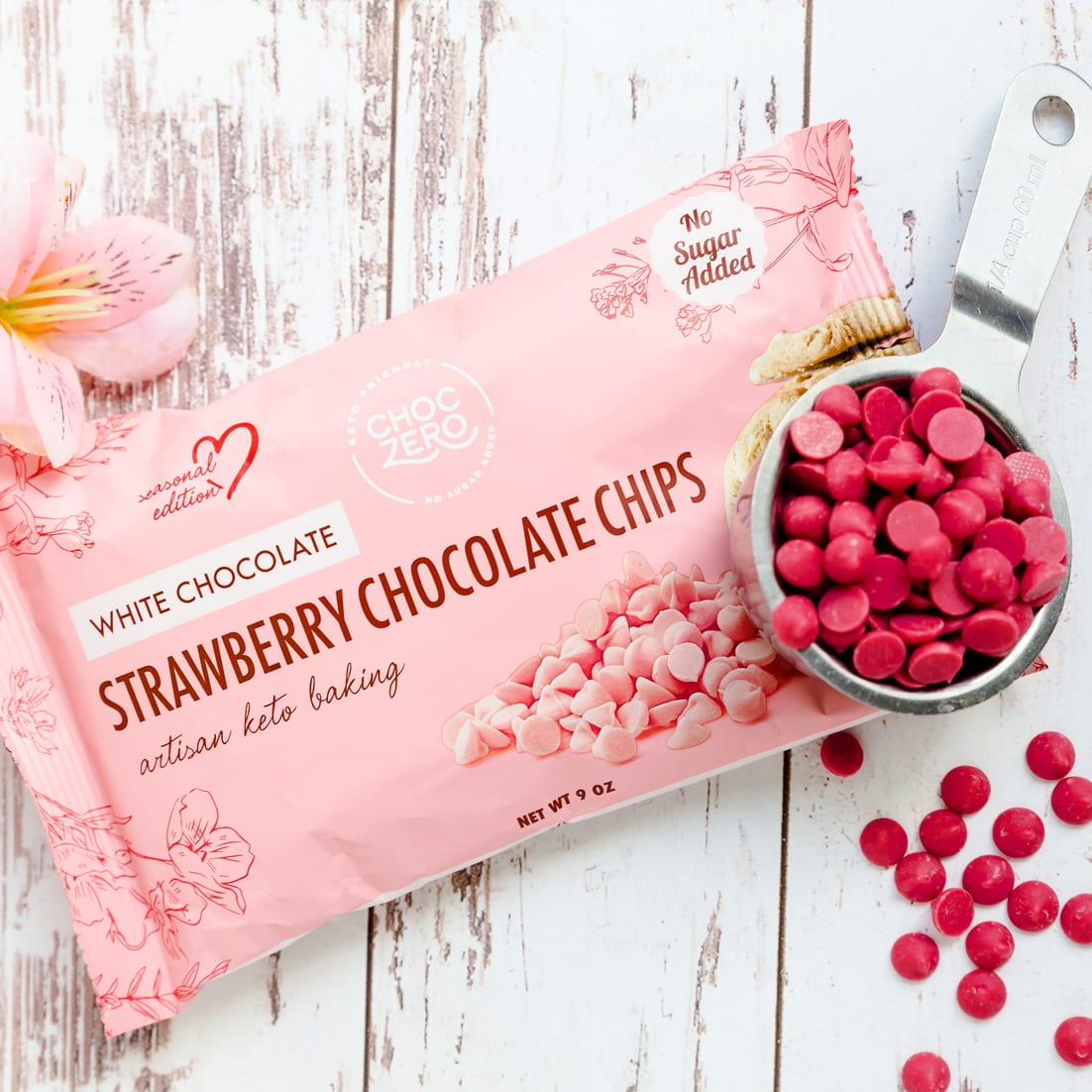 Packaging of Choczero strawberry white chocolate chips next to keto strawberry chocolate chip inside a measuring cup