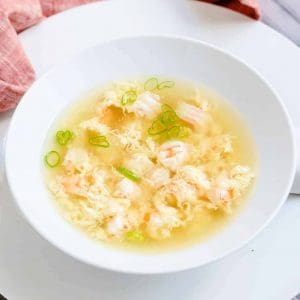 Seafood egg drop soup served in a white soup bowl with soup spoon