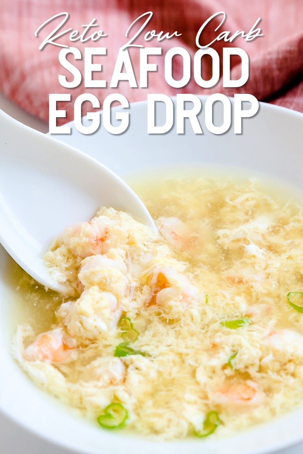 Seafood egg drop soup being scooped up with soup spoon