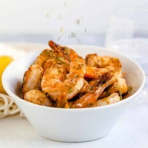 Old Bay Pan Fried Garlic Shrimp in a bowl with dried basil being sprinkled on