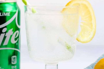 Keto sprite served in a glass with lemon slice top with a straw next to a can of sprite