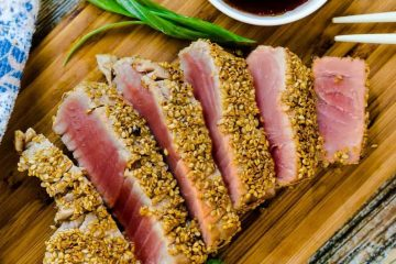 Sesame Crusted Pan Seared Ahi Steaks served on a wooden plank with dipping sauce